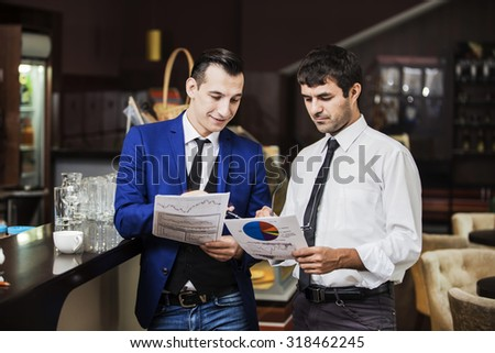 Two young businessman reading documents in a cafe