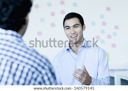 Two young businessman sitting and talking in office - stock photo