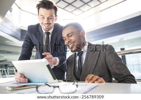 Two young businessmen are discuss plan of work, while looking at the documents. - stock photo