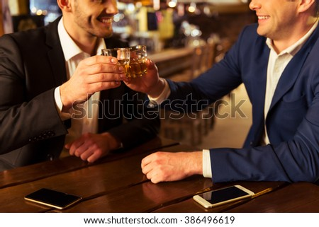Two young businessmen are smiling and clanging glasses of  alcoholic beverage together while sitting in pub - stock photo
