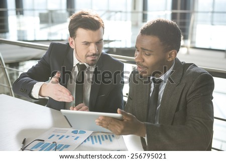 Two young businessmen are working with pc tablet in modern office.