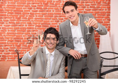 Two young businessmen celebrating successful year