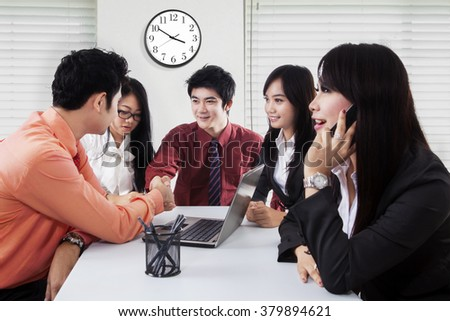 Two young businessmen closing a deal by shaking hands in front of their partners in the office - stock photo