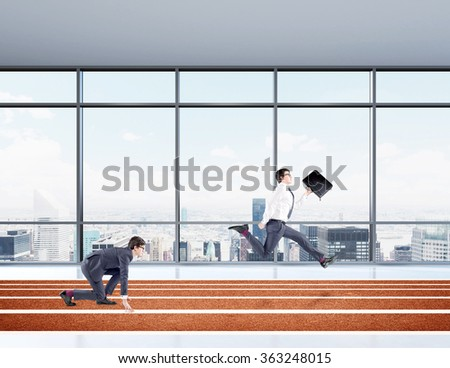 Two young businessmen competing on the track. One in crouch start, the other running forward with a black folder. Paris view in the window at the background. Concept of competition. - stock photo