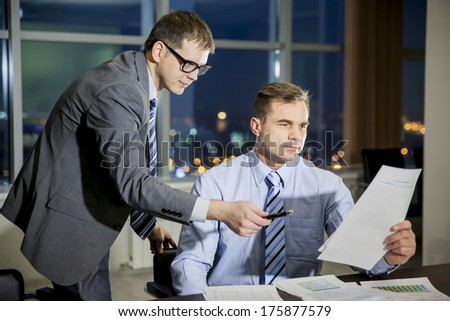 two young businessmen discussing document on meeting