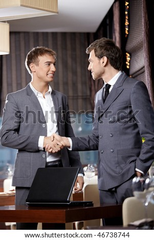 Two young businessmen have met at restaurant - stock photo
