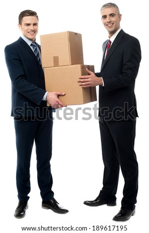 Two young businessmen holding cardboard boxes - stock photo