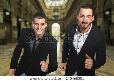Two young businessmen run in city center - stock photo
