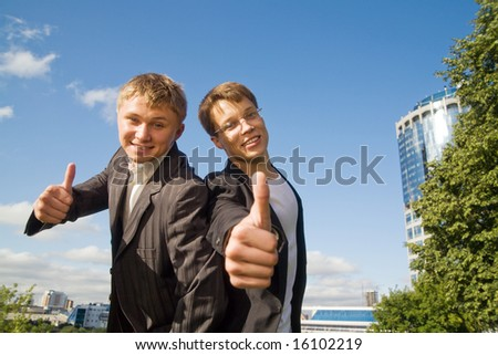 Two young businessmen showing thumb up sign.