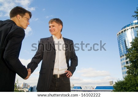 Two young businessmen smiling and shaking hands to each other. - stock photo