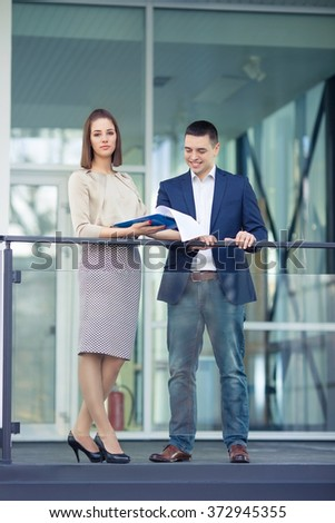 Two young businesspeople discussing paperwork in front of the office