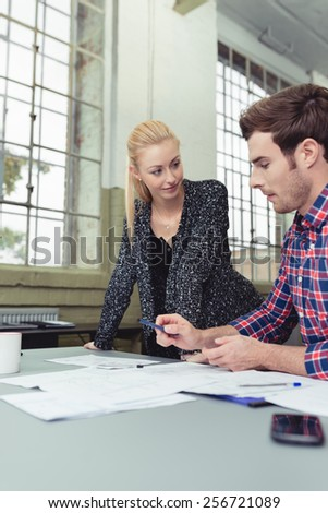 Two young businesspeople having a discussion as they analyse paperwork spread out on the desk in front of them - stock photo