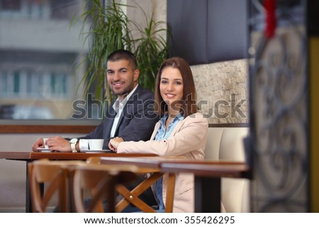 Two young businesspeople on a business meeting in a coffee shop - stock photo