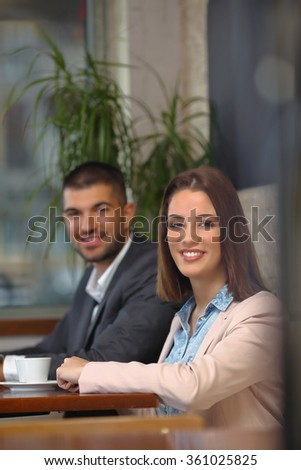 Two young businesspeople on a coffee break or business meeting in a coffee shop - stock photo