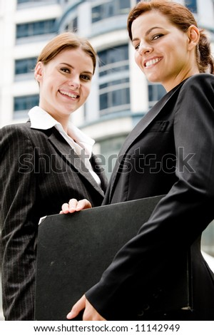 Two young businesswoman in the city with buildings behind