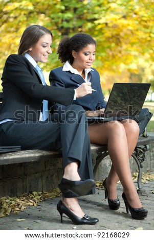 two young businesswoman working on laptop,  outdoor