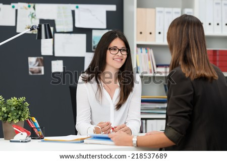 Two young businesswomen having a meeting in the office sitting at a desk having a discussion with focus to a young woman wearing glasses - stock photo