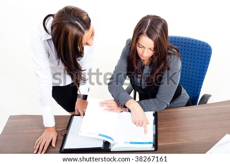 Two young businesswomen, reading in a note-book - stock photo