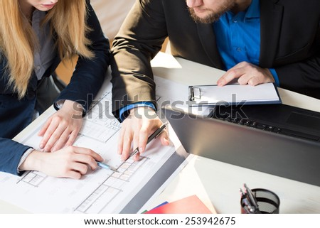 Two young busy architects checking the plan of new building - stock photo