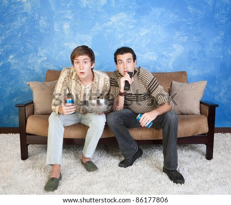 Two young Caucasian friends with drink cans and popcorn watch television - stock photo