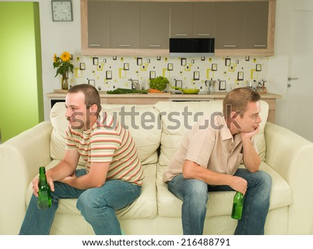 two young caucasian men sitting on couch, acting upset