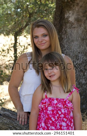 Two young Caucasian sisters in a park. One girl is a teenager and one is a child. - stock photo