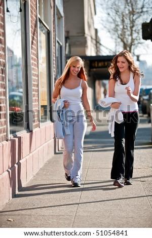 Two young Caucasian women jogging outside - stock photo