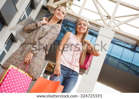 Two young cheerful women with shopping bags outdoors