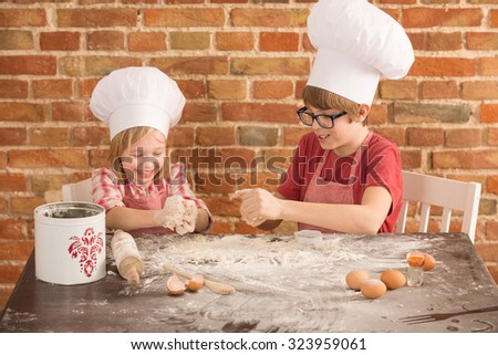 two young chefs, baking a cake