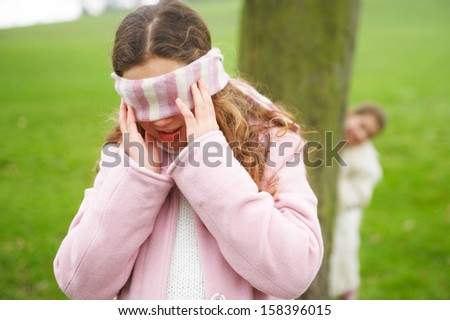 Two young children and family sisters playing hide and seek together in a park with green grass and hiding behind a tree while blindfolded and counting during a cold winter day. - stock photo