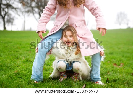 Two young children and family sisters playing together in a park with green grass and bare trees during a cold winter day, wearing coats and having fun outdoors. - stock photo