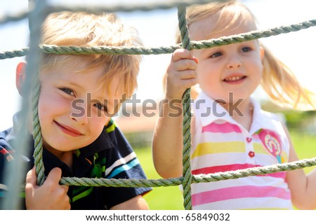 Two young children climbing the net in the playground - stock photo