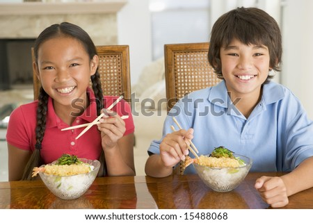 Two young children eating Chinese food in dining room smiling - stock photo