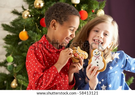 Two Young Children Eating Christmas Treats In Front Of Christmas Tree