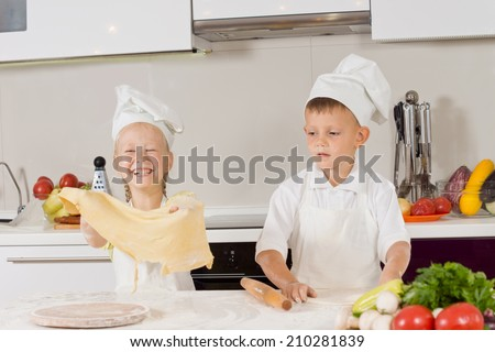 Two young children having fun making pizza with the little girl giggling as she holds aloft a large sheet of pastry that the little boy has just finished rolling out - stock photo