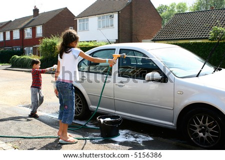 Two young children helping out with washing of the car, using sponge and hose pipe. - stock photo