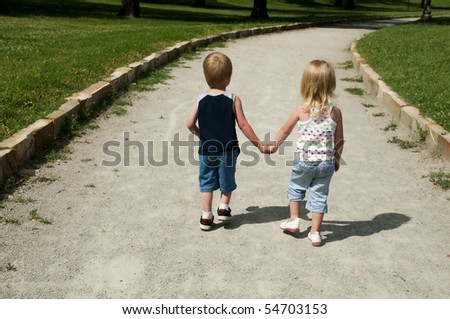 two young children holding hands and walking down a path at the park - stock photo