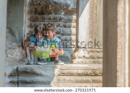 two young children looking at tourist map in Angkor wat, cambodia - stock photo
