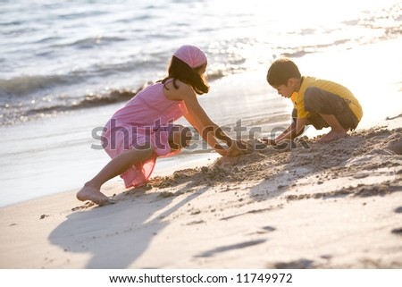 Two young children making sand castle together on a beautiful warm evening by the sea. - stock photo