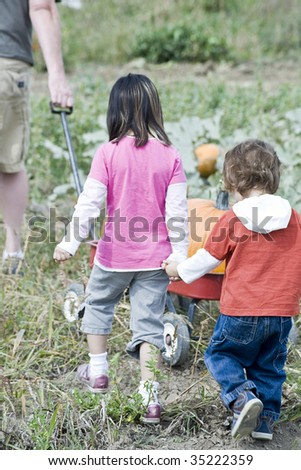 Two young children playing in a Pumpkin patch