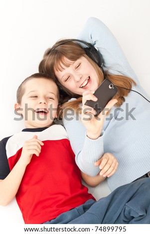 two young children playing on the smart phone - stock photo