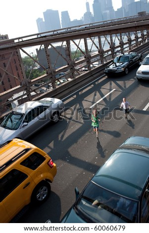 Two young children running in between cars on a busy city bridge.