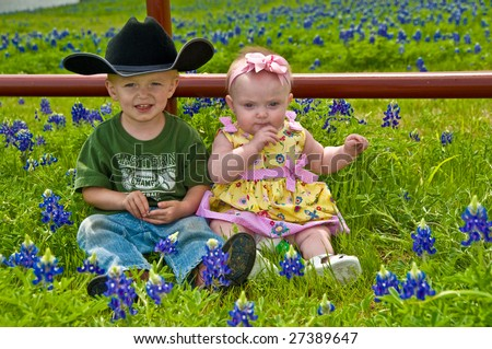 Two young children sit together in a meadow covered with bluebonnet flowers - stock photo