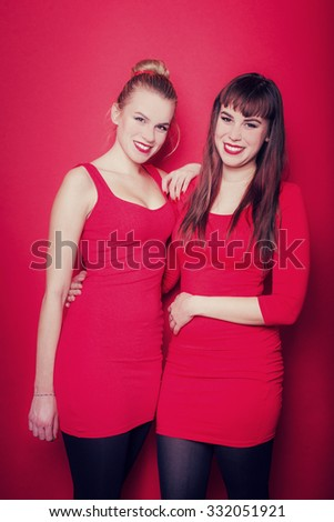 Two young christmas women on a red background - stock photo