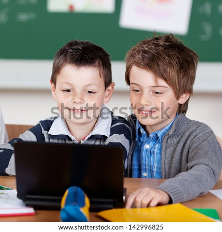 Two young classmates studying with laptop at the classroom - stock photo