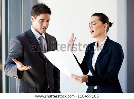two young colleagues arguing over paperwork in office - stock photo