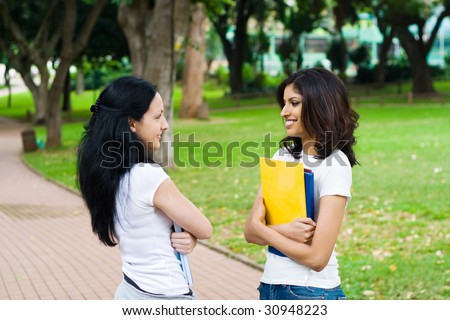 two young college students talking in school campus - stock photo