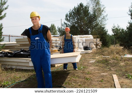 Two young construction workers in hardhats and overalls carrying a wall insulation panel on a building site - stock photo