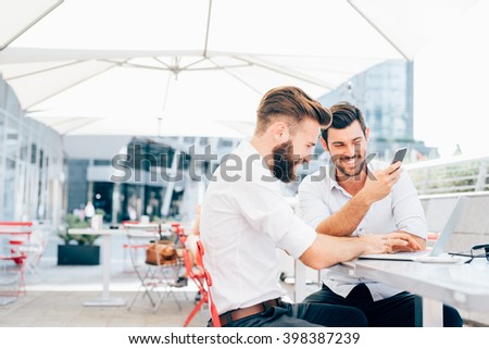 Two young contemporary businessmen working outdoor sitting in a bar using a smart phone and a notebook, both smiling - technology, business, work concept - copy space on left - stock photo