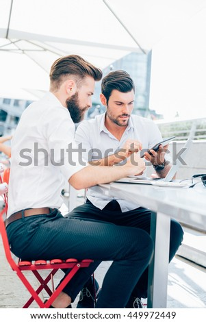 Two young contemporary businessmen working outdoor sitting in a bar using a smart phone and a notebook, discussing - technology, business, work concept - stock photo